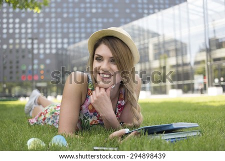 Happy Pretty Teen Girl Wearing Hat, Lying on her Stomach on the Green Grass and Smiling Into Distance. - stock photo