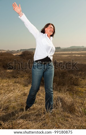 Happy pretty woman middle aged enjoying outdoors. Feeling free. Clear sunny spring day with blue sky. - stock photo