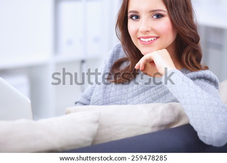 Happy pretty woman using laptop sitting on  sofa - stock photo