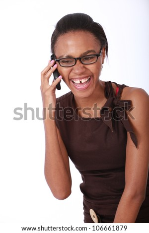 Happy pretty young African American business woman or colleague with tooth gap wearing a smart brown dress and glasses talking and laughing on a mobile cellular telephone isolated on white background