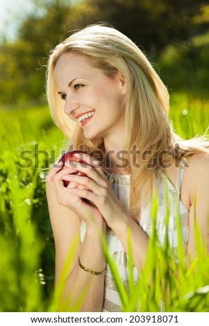 Happy pretty young girl with beautiful smile and blond hear sitting at the spring green grass and holding red apple.