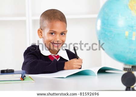 happy primary school boy in classroom - stock photo