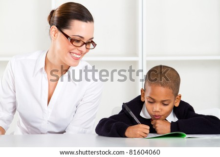 happy primary school teacher and pupil - stock photo