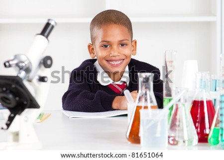 happy primary schoolboy in science lab - stock photo