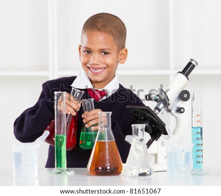 happy primary schoolboy in science lab - stock photo