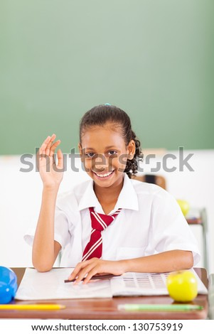 happy primary schoolgirl hand up classroom
