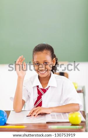 happy primary schoolgirl hand up classroom - stock photo