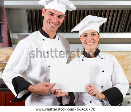 happy professional chefs holding white board in kitchen - stock photo