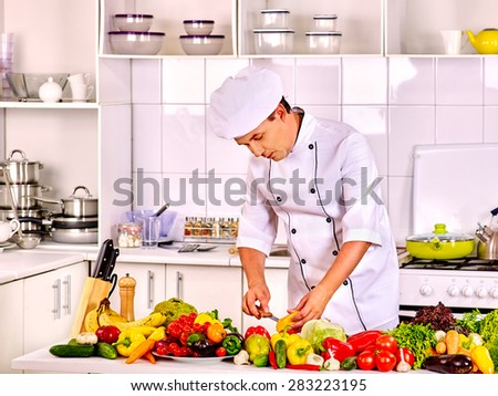 Happy professional cook man in chef hat is cooking . - stock photo