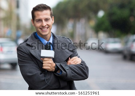 happy professional news reporter portrait in the city in the rain - stock photo