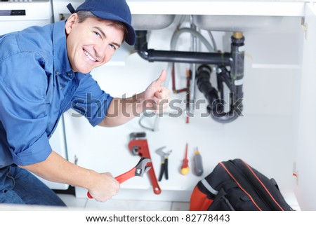 Happy professional plumber doing sink reparation. Contractor. - stock photo