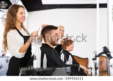 Happy professional woman hairdresser doing hairstyle for young men - stock photo