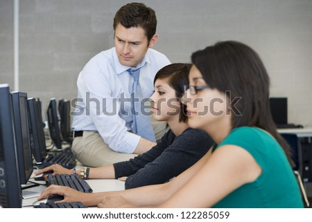 Happy professor watching students' work in computer lab