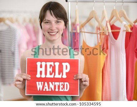 Happy proud owner of store with help wanted sign - stock photo