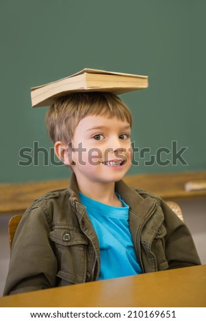 Happy pupil balancing book on his head at desk at the elementary school - stock photo