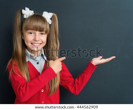 Happy pupil - cute girl showing something in front of a big chalkboard. Back to school concept.