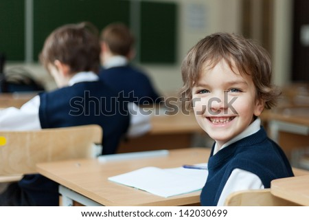 Happy Pupil in uniform sitting at  desk in school classroom - stock photo
