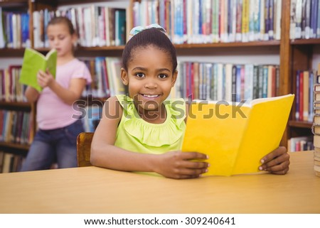 Happy pupil reading a library book at the elementary school - stock photo