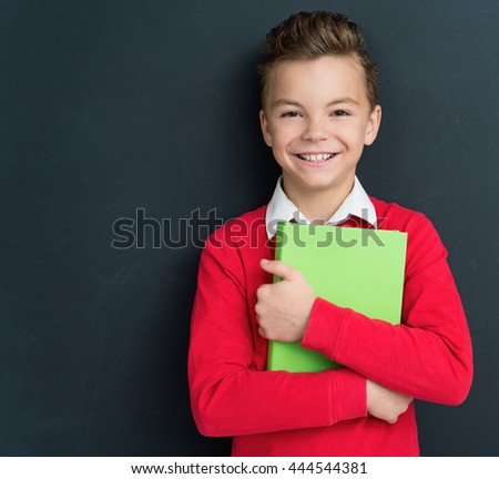 Happy pupil - teen boy posing with books in front of a big chalkboard. Back to school concept.  - stock photo
