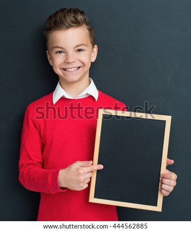 Happy pupil - teen boy posing with small blackboard in front of a big chalkboard. Back to school concept. - stock photo