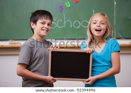 Happy pupils holding a school slate in a classroom - stock photo