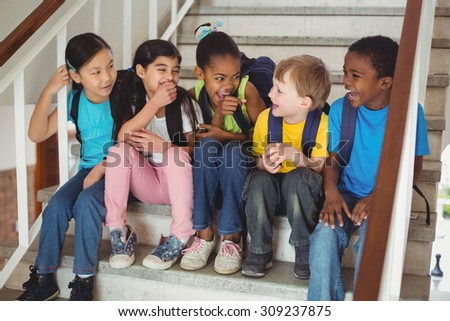Happy pupils laughing and sitting on stairs in school - stock photo