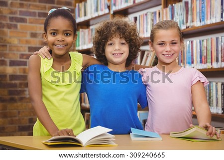 Happy pupils reading a library book at the elementary school - stock photo