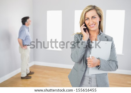 Happy realtor calling someone with her mobile phone in empty house with potential buyer smiling at camera - stock photo