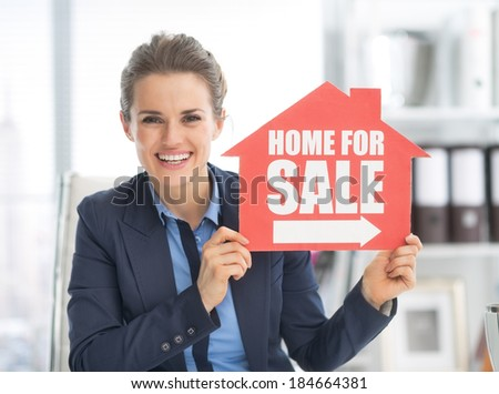 Happy realtor woman showing home for sale sign