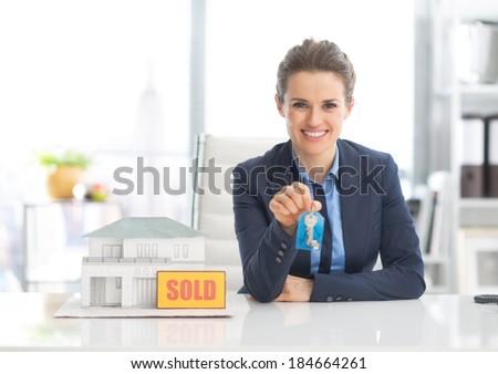 Happy realtor woman showing keys - stock photo