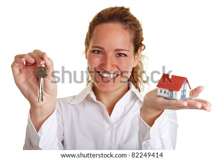 Happy realtor woman with small house and keys - stock photo