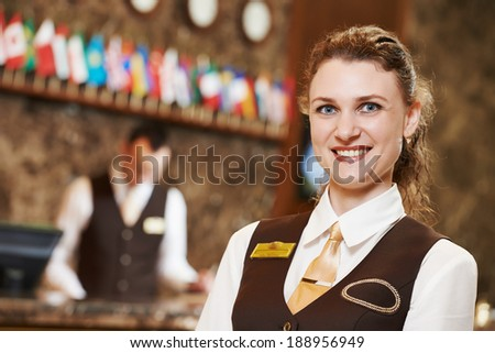 Happy receptionist female worker portrait standing at hotel counter in lobby - stock photo