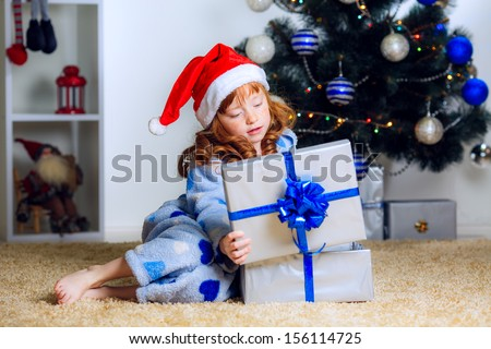 Happy red-haired girl in a Christmas hat and pajamas at home opens a gift under the tree - stock photo