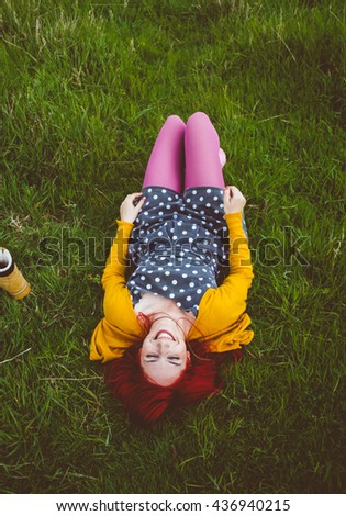 Happy red haired woman dressed in stylish dress and yellow cardigan and pink stockings,laying carefree in the vivid field - stock photo