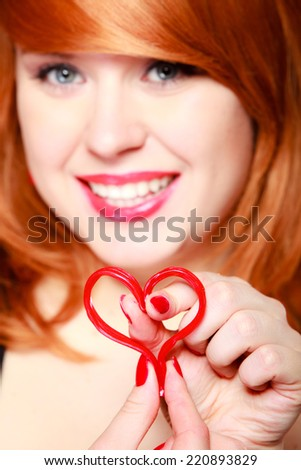 Happy redhaired girl holding red heart love symbol. Young woman in love. Valentines day.