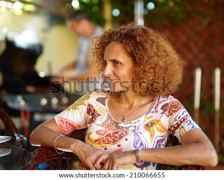 Happy redhead curly hair caucasian woman smiling - stock photo