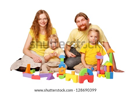 Happy redhead father, mother and two children building from toy blocks. Family concept. Isolated on white background