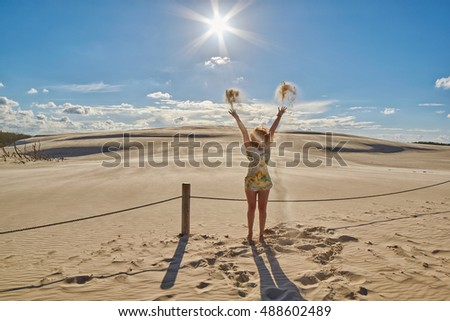 Happy Redhead Lady waving hands against Sunset at Sand Dunes in Leba, Poland