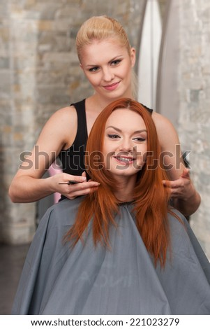 Happy redhead woman getting a new haircut. Beautiful blond hairdresser giving new haircut to female customer at parlor - stock photo