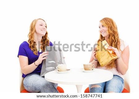 happy redhead women sitting at a coffee table with shopping bags on white background - stock photo