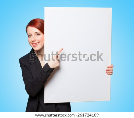Happy redhead women with white board on blue background. - stock photo