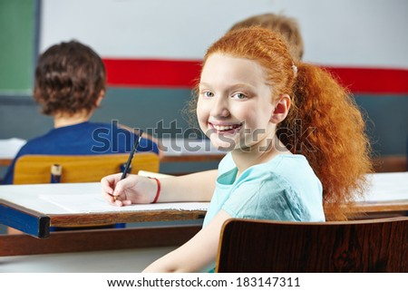 Happy redheaded girl smiling in elementary school class