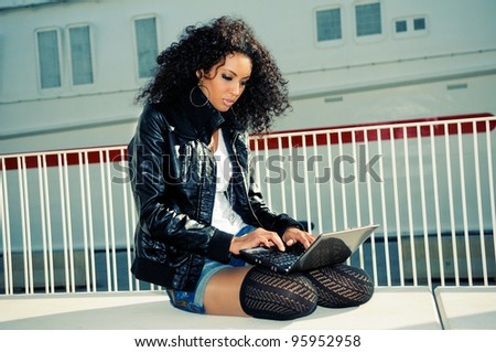 Happy relaxed african girl using a laptop in the street - stock photo