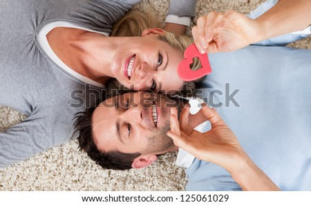 Happy relaxed attractive man and woman lying on their backs head to head on a white carpet smiling up at the camera - stock photo