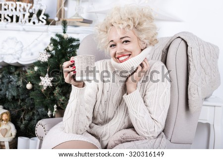 Happy relaxed beautiful stylish blonde woman is sitting in a comfortable chair beige knitted. Decorated home interior. Christmas tree. Series of winter holiday photos.  - stock photo