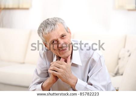 Happy relaxed elderly  man on sofa - stock photo