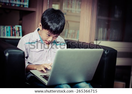 Happy relaxed little boy with a friendly smile sitting on a sofa at library on his laptop computer - stock photo
