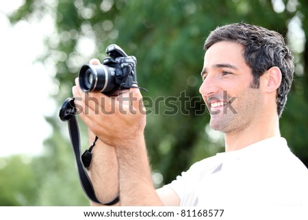 Happy relaxed man looking at the screen of his DSLR camera as he takes a photograph - stock photo