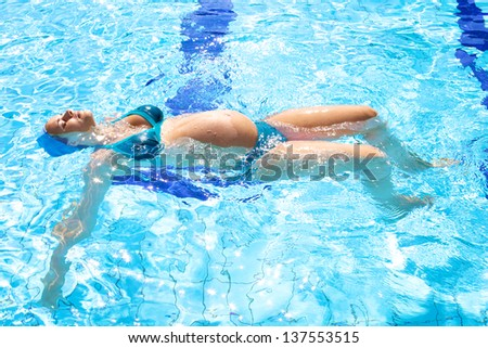 Happy relaxed pregnant woman swimming happy in beautiful swimming pool - stock photo