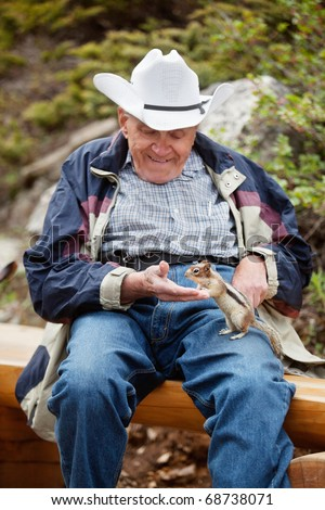 Happy relaxed senior man playing with squirrel - focus on squirrel - stock photo